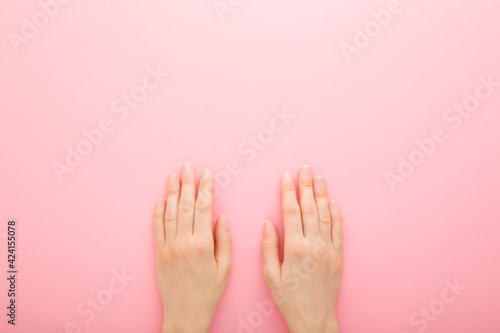 Photo Young adult woman hands on light pink table background