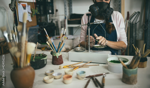 Fototapeta Caucasian woman mixing painting colors with a vintage balance inside her creative pottery studio - Soft focus on hands obraz