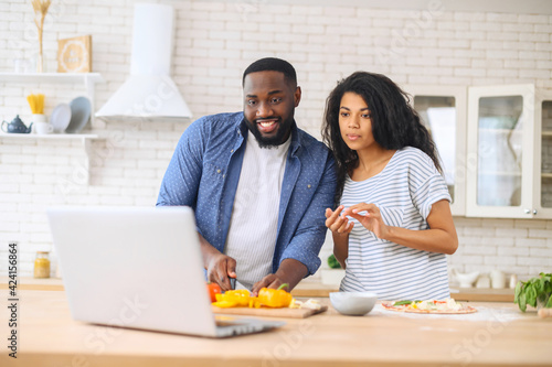 Fototapeta Interested young mixed-race couple attentively watching online cooking classes, learning how to make dinner lunch pizza, watching video blog course from laptop in the kitchen, preparing vegetables obraz