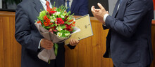 Men In Business Suits - Officials, Businessmen, Teachers Or Lawyers - Participants In The Awards Ceremony. Presentation Of A Certificate Of Honor And A Bouquet Of Flowers