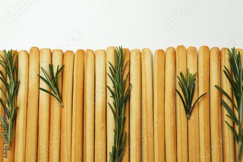 Fototapeta Grissini breadsticks with rosemary on white background