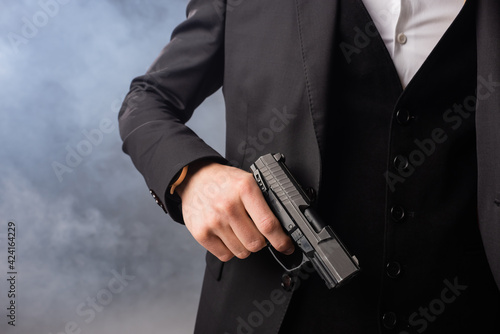 Obraz partial view of businessman with gun on grey background with smoke - fototapety do salonu