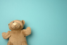 Old Teddy Bear With A Band-aid On The Eye Lies On A Blue Background