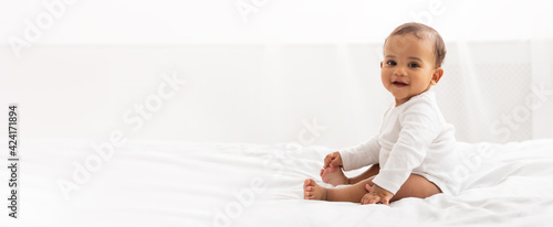 Fotografia Happy Black Little Baby Girl Sitting In Bedroom At Home