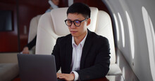 Rich Asian Businessman Flying First Class And Working On Plane With Laptop