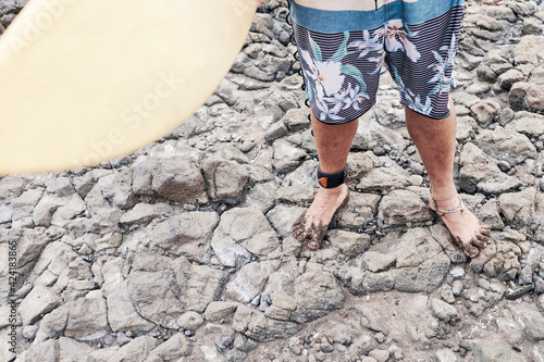 Surfer, Surfboard And Feet Cover In Sand On Rocky Shore