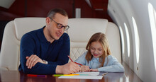 Father And Daughter Drawing With Colorful Pencils Flying Together On Private Jet