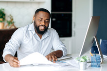 Busy Successful African American Man, Entrepreneur Or Lawyer, In Formal Wear, Sits At Work Desk, Uses Computer For Work, Studies Financial Documents, Analysis Profit And Strategy Of Company