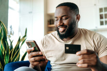 A Satisfied Smiling African American Guy, In Casual Clothes, Sits On The Couch At Home, Holds A Phone And A Credit Card In Hands, Pays For Online Purchases, Enters A Card Number, Online Shopping