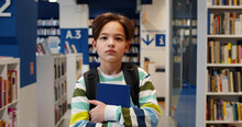 Portrait Of Schoolboy With Backpack Carrying Books Walking In School Library