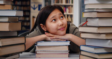 Happy Asian School Student Sitting In Library Leaning On Pile Of Books