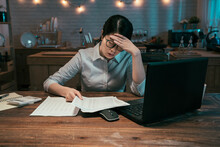 Tired Asian Chinese Businesswoman Working On Laptop Computer Until Night. Portrait Of Casual Stressed Lady With Headache At Dining Table In Home Kitchen. Exhausted Female Freelancer Holding Documents
