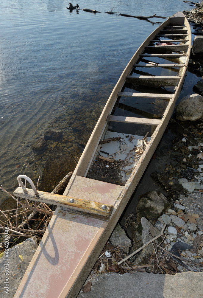 Fototapeta old wooden longboat partly submerged in water