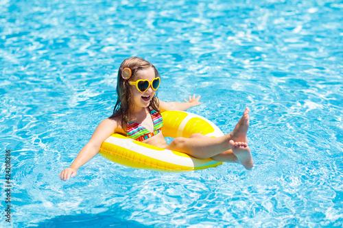 Obraz Child in swimming pool on ring toy. Kids swim. - fototapety do salonu