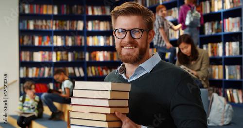 Fotografie, Obraz Bearded school teacher or librarian holding books in hands standing in library interior