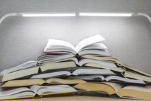 Many Open Books Lie On The Table Under Two Lamps. Concept Of Learning, Distance Learning During A Coronavirus Pandemic.