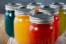 A View Of Several Mason Glass Jars With A Variety Of Colored Liquid Contents Inside.