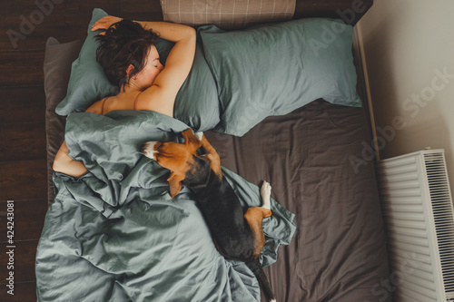 Fototapeta Beautiful young girl sleeps in the morning in bed with her pet.
