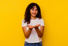 Young Mixed Race Woman Isolated On Yellow Background Holding Something With Palms, Offering To Camera.