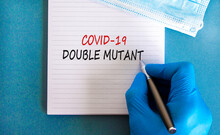 Covid-19 Double Mutant Symbol. Doctor Hand In Blue Glove With White Note. Concept Words 'Covid-19 Double Mutant'. Medical Mask. Medical And COVID-19 Pandemic Double Mutant Concept. Copy Space.