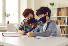 School Children Wear Mouth Covering Face Masks During Coronavirus Infection Outbreak. Creative Students Communicating, Drawing, Writing And Helping Each Other. Two Little Boys Get Distracted In Class