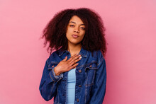 Young African American Woman Isolated On Pink Background Taking An Oath, Putting Hand On Chest.