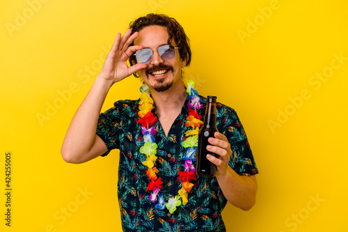 Young caucasian man wearing a hawaiian necklace holding a beer isolated on yellow background excited keeping ok gesture on eye.