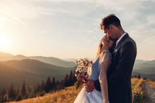 Loving Wedding Couple Hugging In Mountains At Sunset. Portrait Of Young Bride And Groom In Summer Carpathians.