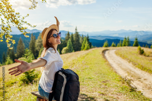 Obraz Trip to Carpathian mountains. Woman hiker relaxing admiring landscape with arms raised. Traveling in summer Ukraine - fototapety do salonu