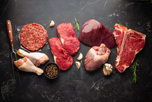 Selection Of Assorted Raw Meat Food With Seasonings For Zero Carb Carnivore Diet: Uncooked Beef Steak, Ground Meat Patty, Heart, Liver And Chicken Legs On Black Stone Background From Above