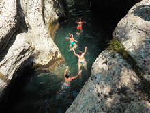 A Company Of People Swims Along The Sunlit River Between The Canyons. Canyon White Cliffs