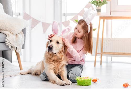 Obraz Little girl with golden retriever dog at Easter - fototapety do salonu