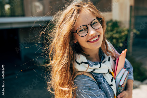 Fototapeta Candid portrait of a happy young student woman with long red hair smiling and wearing transparent eyeglasses standing next to the unversity and carrying lots of books and folders on a sunny day