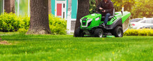 Gardener Ride On A Lawn Mowing Tractor Drives And Mows A Lawn With Green Grass.