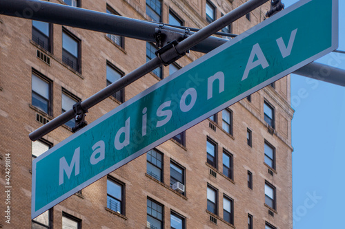 Photo hanging green and white city street sign of Madison ave, avenue