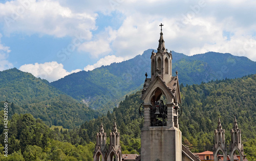 Canvastavla CAMPANILE BETWEEN THE MOUNTAINS AND GREEN MEADOWS AND THE BLUE SKY WITH WHITE CL