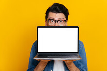 Amazed Excited Caucasian Guy With Glasses Peeking Out From Behind Laptop, Looks Surprised At Camera, Stands On Isolated Orange Background, Holds An Open Laptop With Blank White Screen, Copy Space