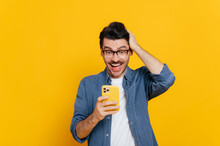 Cheerful Excited Modern Positive Caucasian Guy Uses His Smartphone, Texting With Friends, Browsing Internet, Social Networks, Get Unexpected News, Stands On Isolated Orange Background, Smiling