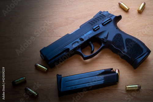 Fotografering firearm, 40 caliber pistol in ammunition on wooden surface.