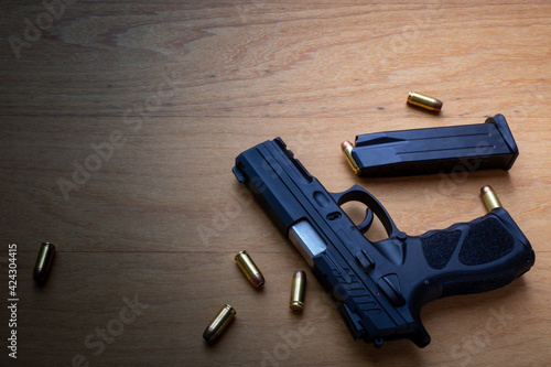 Photo firearm, a pistol with a pistol magazine and ammunition on top of the wooden surface