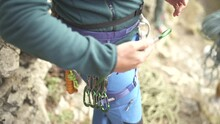 Rock-Climber Clipping Quickdraws To His Harness