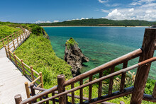 Lush Maritime Landscape With Corals Around A Rock, Emerald Green Sea, Mountain And Tsukihama Beach In The Background. View From The Top Of The Lookout Stairs. Wooden Path To Contemplate The Landscape.