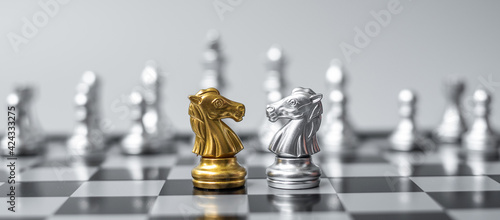 Gold and silver Chess Knight (horse) figure on Chessboard against opponent or enemy Fototapet