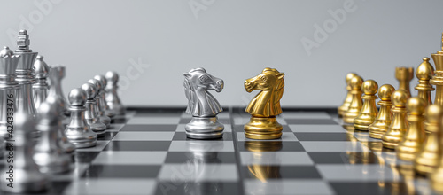 Photo Gold and silver Chess Knight (horse) figure on Chessboard against opponent or enemy