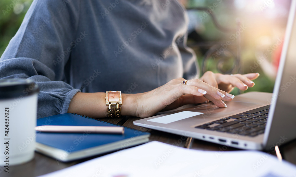 Close-up of young businesswoman in casual clothing using compute laptop while she working outdoors - obrazy, fototapety, plakaty