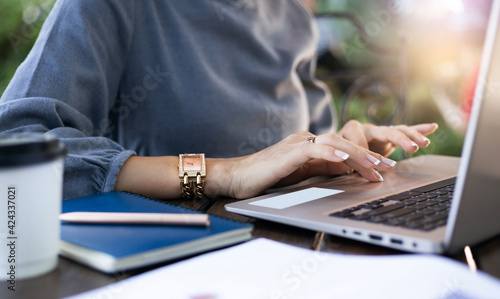Fototapeta Close-up of young businesswoman in casual clothing using compute laptop while she working outdoors obraz na płótnie