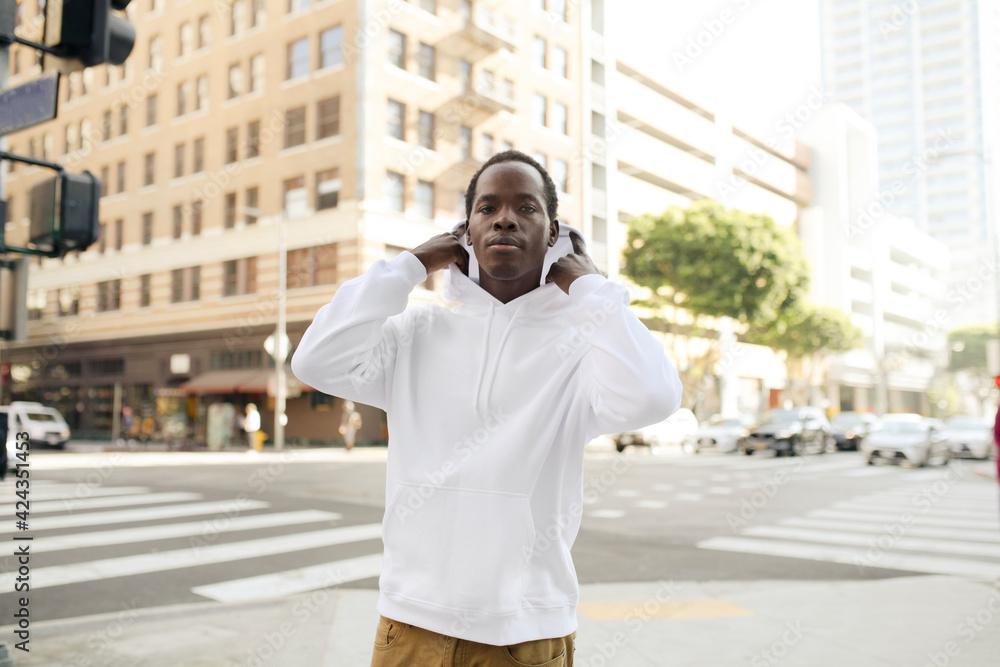 Fototapeta Trendy hoodie on man with brown pants in the city