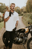 Tattooed biker standing by his vintage motorcycle