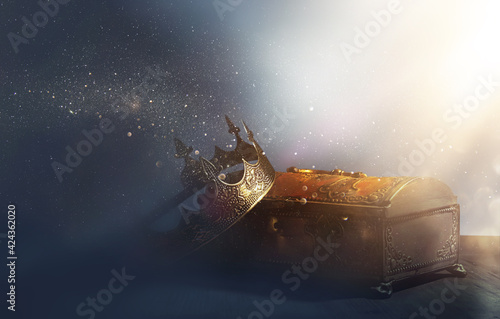 low key image of beautiful queen or king crown over gold treasure chest Fototapeta