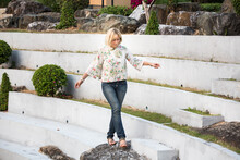 Blonde European Girl Spends Her Holiday Actively In The Asian Park, Walking And Having Fun.